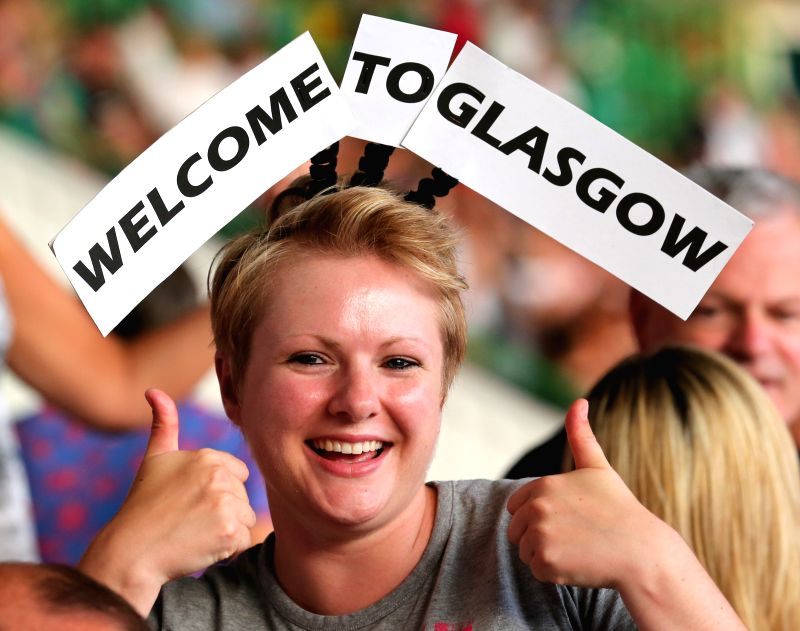 """A spectator wears a sign of """"Welcome to Glasgow"""" during the opening ceremony of the XX Commonwealth Games at the Celtic Park in Glasgow, Britain, on July ."""
