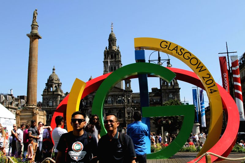 People pose for pictures with a logo of the Commonwealth Games before the opening ceremony of the XX Commonwealth Games at the Celtic Park in Glasgow, Britain, July