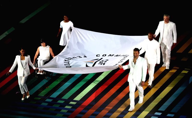 The Commonwealth Games flag is carried into the stadium during  the opening ceremony of the XX Commonwealth Games at the Celtic Park in Glasgow, Britain, on July ...
