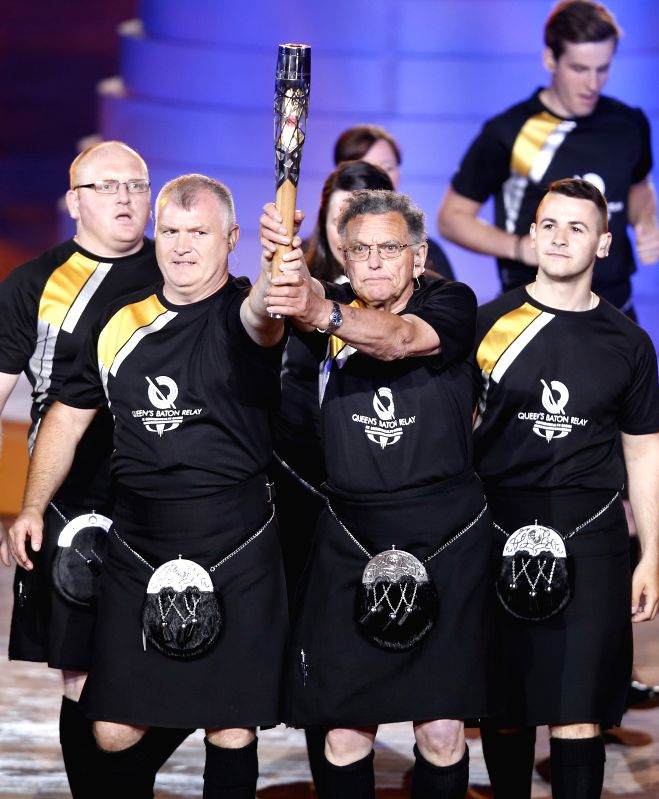 The Queen's baton is carried during the opening ceremony for the XX Commonwealth Games at the Celtic Park in Glasgow, Britain, on July 23, 2014. (Xinhua/Wang ...