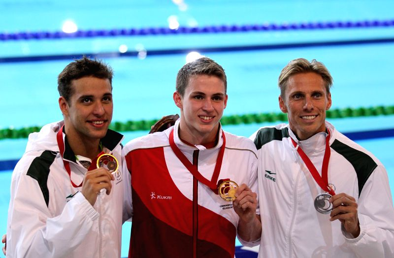 Benjamin Proud(C) of England shows his gold medal during the awarding ceremony for Men's 50M Butterfly Final during day 2 of the Glasgow 2014 Commonwealth Games at ..