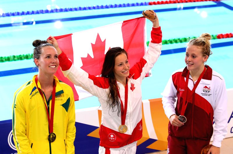 Katerine Savard (C) of Cananda celebrates with the national flag of Canada during the awarding ceremony for the Women's 100M Butterfly Final during day 2 of the ...