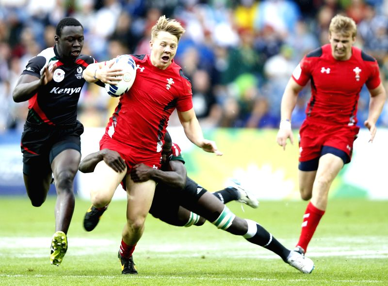 James Davies(2nd L) of Wales is tackled by Oscar Ouma Achieng (2nd R) of Kenya in the plate semi final match between Wales and Kenya of Men's Rugby Sevens during ...