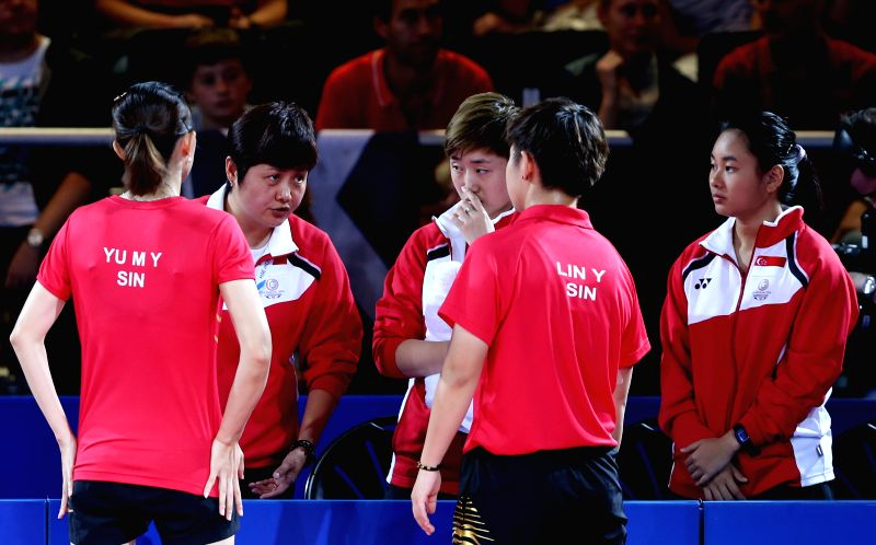 Jing Junhong (2nd L), coach of Singapore, instructs to Lin Ye (2nd R) / Yu Mengyu (1st L) of Singapore during the women's team final of table tennis against ...