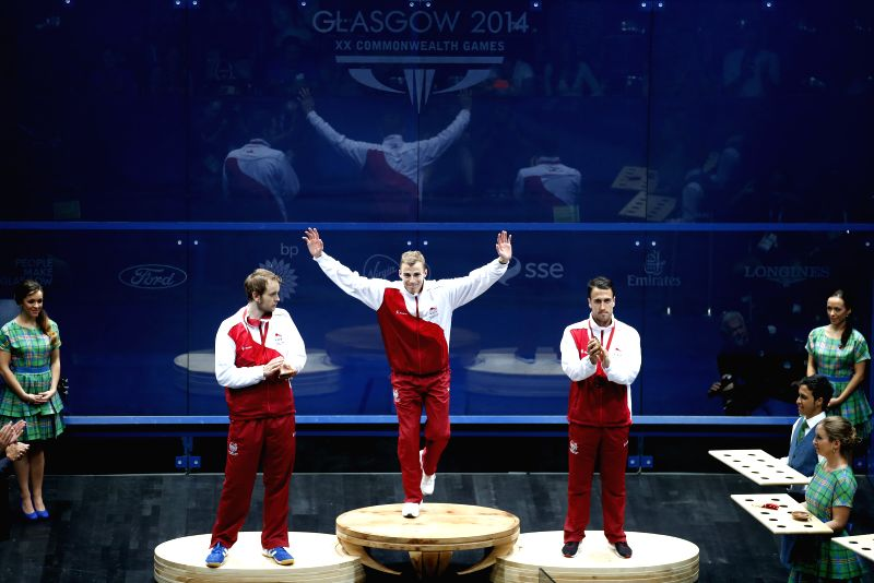 Gold medalist Nick Matthew(C) of England waves during the medal ceremony for the Men's Singles of Squash on day 5 of the Glasgow 2014 Commonwealth Games at ...