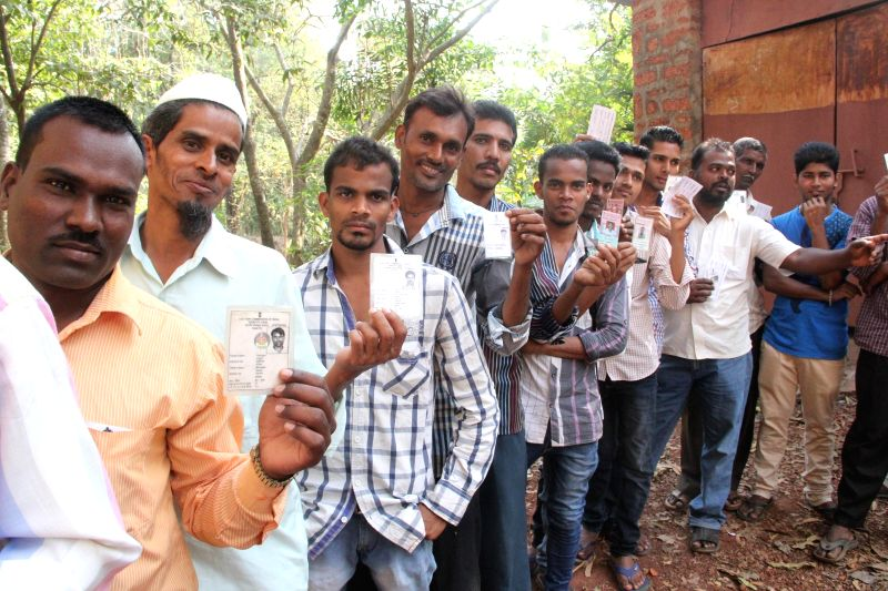 People queue-up to cast their votes at a polling booth in Goa during the zilla panchayat elections on March 18, 2015.