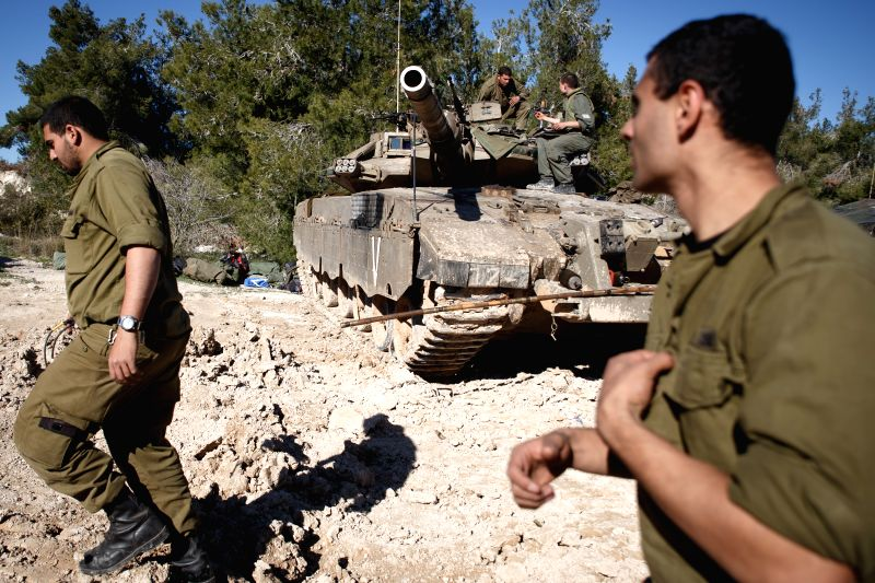 Israeli soldiers walk past a Merkava tank near the border between Israel-occupied Golan Heights and Lebanon, on Jan. 21, 2015. Israel has put on alert its air