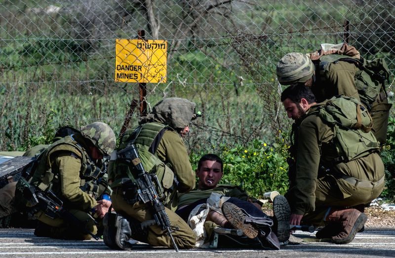 Injured Israeli soldiers receive medical treatment after an anti-tank missile hit an Israeli army vehicle near the Israel-Lebanon border, on Jan. 28, 2015. ...