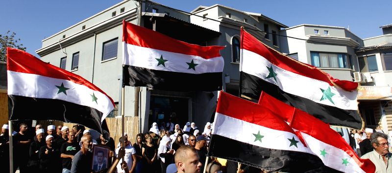 GOLAN HEIGHTS, July 27, 2018 - Druzes hold Syrian flags during a rally in Buq'ata near the ceasefire line between Israel and Syria in the Israeli-occupied Golan Heights, on July 27, 2018.