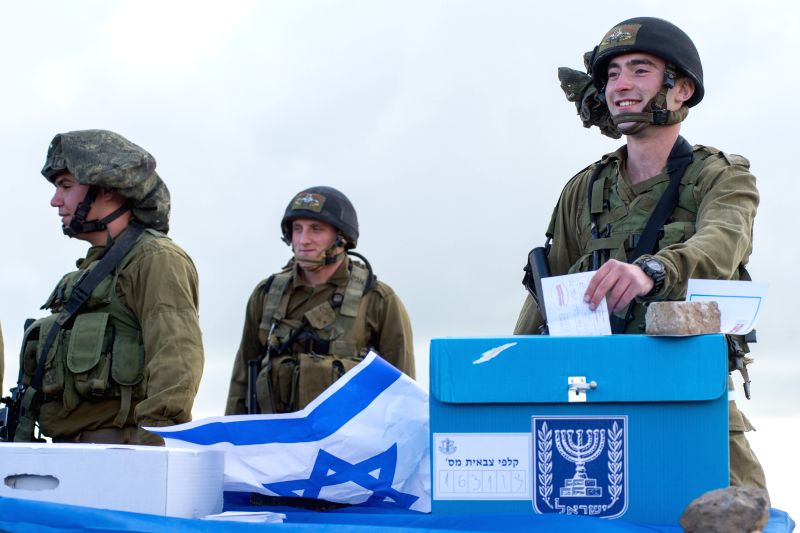 An Israeli soldier casts his ballot two days early at an army base on the Golan Heights, close to the border with Syria, on March 15, 2015. Most soldiers ...