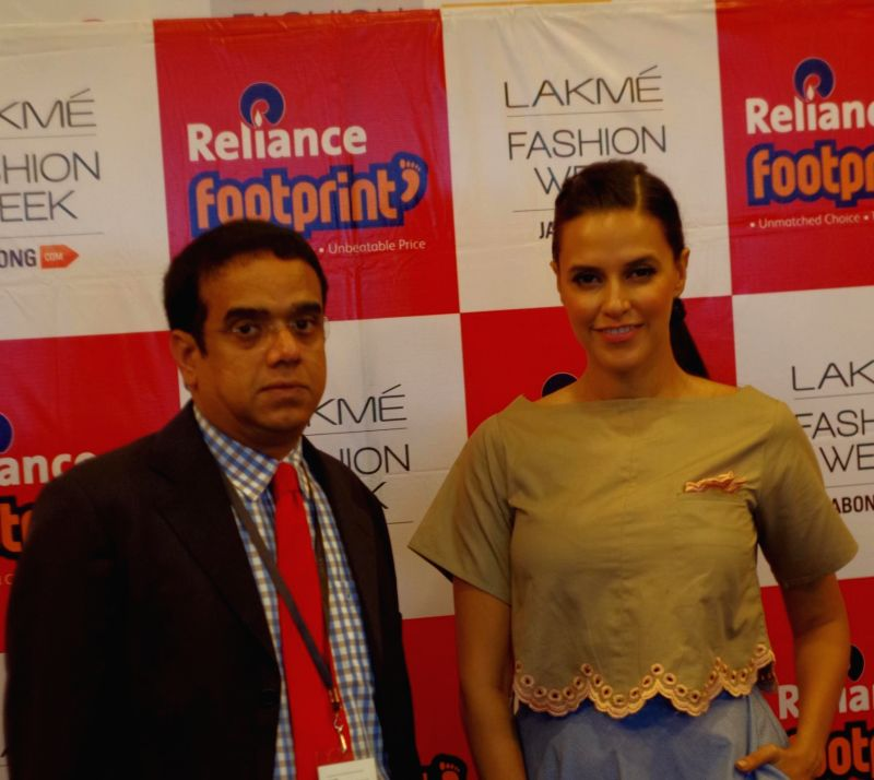Gopalakrishnan Sankar,CEO Reliance Footprint and actress Neha Dhupia unveil Reliance Footprints Winter Autumn 2014 Collection at Lakme Fashion Week in Mumbai on Aug 22, 2014. - Neha Dhupia