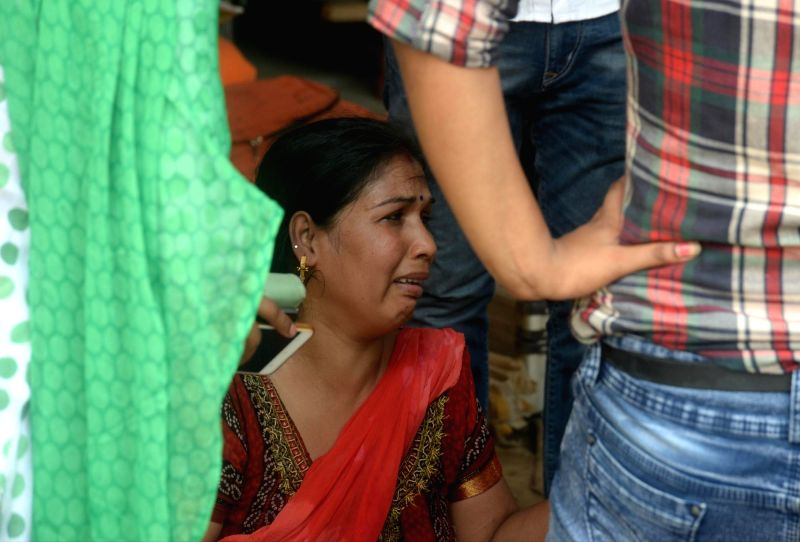 Greater Noida: A grief struck relative of a victim at the site where two buildings collapsed in Greater Noida, on July 18, 2018. At least 50 people were believed trapped under the concrete rubble of ...