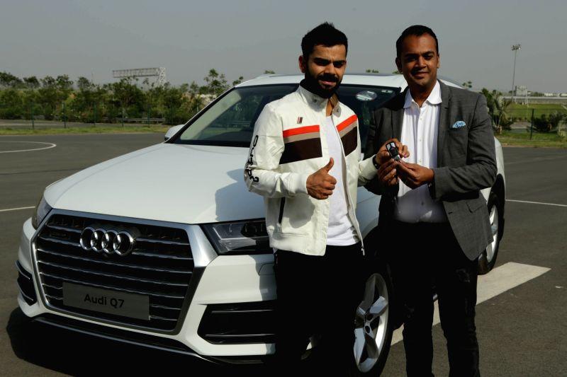 Greater Noida: Indian cricketer Virat Kohli with his new Audi Q7 45 TDI at Buddh International Circuit in Greater Noida on May 11, 2017. - Virat Kohli