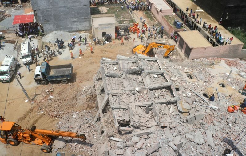 Greater Noida: Rescue operations underway at the site where two residential buildings collapsed on Tuesday evening in a village in Greater Noida;  on July 18, 2018. At least 50 people were believed ...