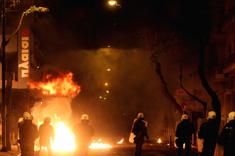 Greek riot police act beside a fire set by protesters during clashes following a rally commemorating the killing of a 15-year-old student back in 2008, in Athens, ...