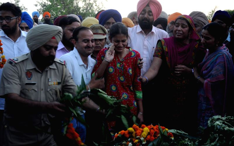 Grief struck family members of martyr Raghbir Singh pay their last respect to him at Sathiala in Amritsar on April 25, 2017. - Raghbir Singh
