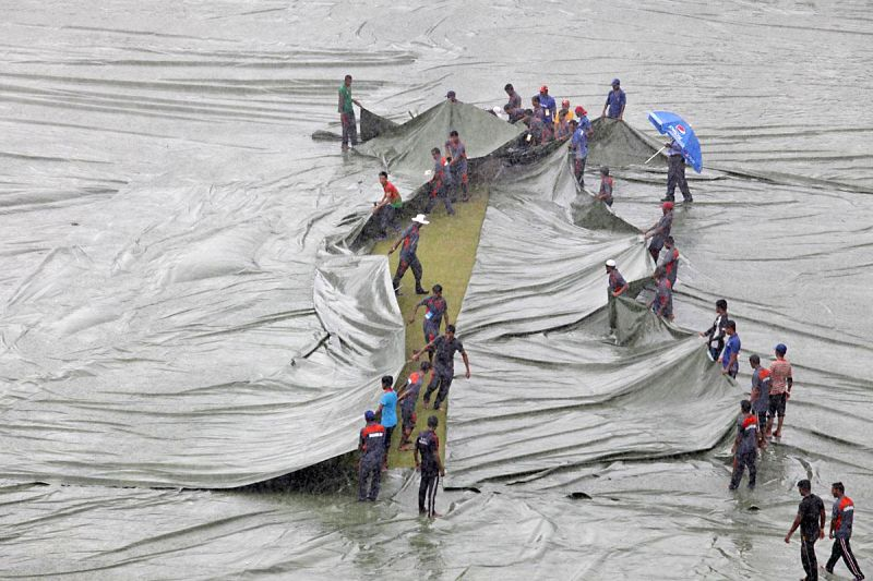 Ground staff cover the field at Sher-e-Bangla National Cricket Stadium as rains disrupt the third One Day International (ODI) match between India and Bangladesh in Dhaka, Bangladesh on June 19, 2014.