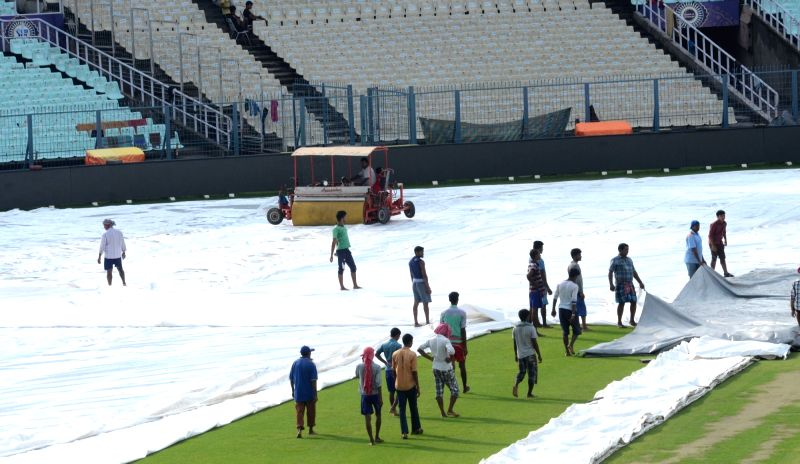 Groundsmen cover the ground with tarpaulin sheets as rain postponed Kolkata Knight Riders practice session at Eden Gardens in Kolkata on May 21, 2016.