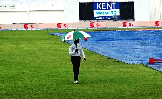 Groundsmen cover the ground with tarpaulin sheets as rain postponed the second test match between India and West Indies at Kingston, Jamaica, on Aug 1, 2016.