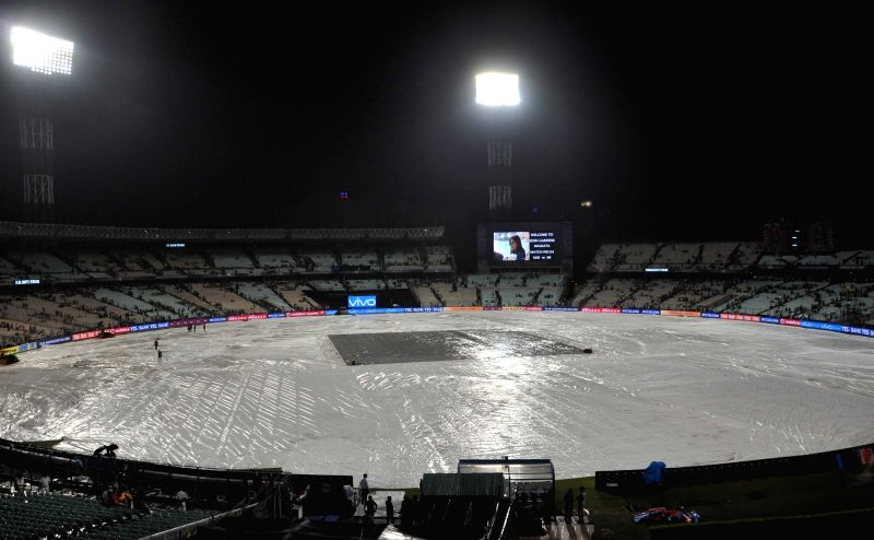 Groundsmen cover the ground with tarpaulin sheets due to rain ahead of an IPL 2017 match between Kolkata Knight Riders and Mumbai Indians at Eden Gardens in Kolkata, on May 13, 2017.