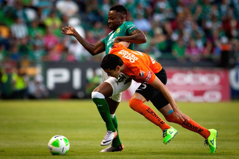 Leon's Eisner Loboa (L) vies for the ball with Pachuca's Daniel Arreola during the first leg of the 2014 Liga MX Closing Tournament match at Nou Camp Stadium in ..