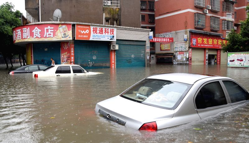 GUANG'Cars are immersed in water on a flooded road in Yuechi County of Guang'an City, southwest China's Sichuan Province, Aug. 26, 2014. A rainstorm hit the county on ...