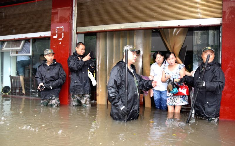 GUANG'Rescuers try to transfer trapped people on a flooded road in Yuechi County of Guang'an City, southwest China's Sichuan Province, Aug. 26, 2014. A rainstorm hit the