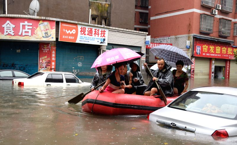 GUANG'Rescuers try to transfer trapped people with a rubber dinghy on a flooded road in Yuechi County of Guang'an City, southwest China's Sichuan Province, Aug. 26, ...