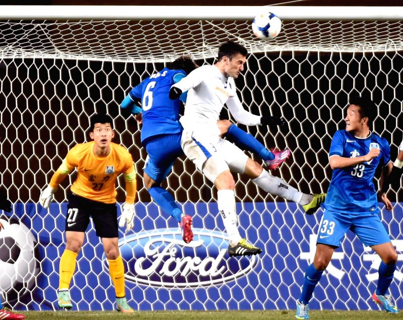 Marin Cidosevic (2nd R) of Singapore's Warriors FC heads the ball during an AFC Champions League football match against China's Guangzhou R&F in Guangzhou, ...