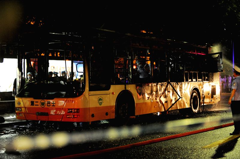 Photo taken on July 15, 2014 shows the burned bus in Guangzhou, capital of south China's Guangdong Province. Two people died and 25 were injured in a bus ...