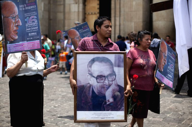 People participate in a march to commemorate the 16th anniversary of the murder of Bishop Juan Jose Gerardi, in Guatemala, capital of Guatemala, on April 26, ...