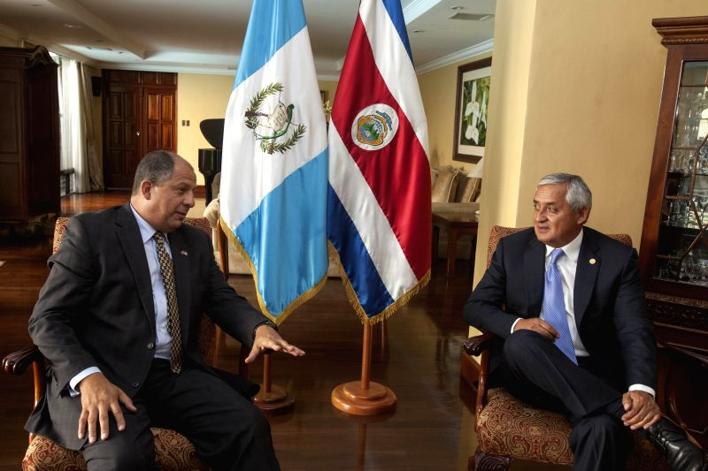 Guatemala's President Otto Perez Molina (R) talks with elected Costa Rican President Luis Guillermo Solis during their meeting in Guatemala City, capital of