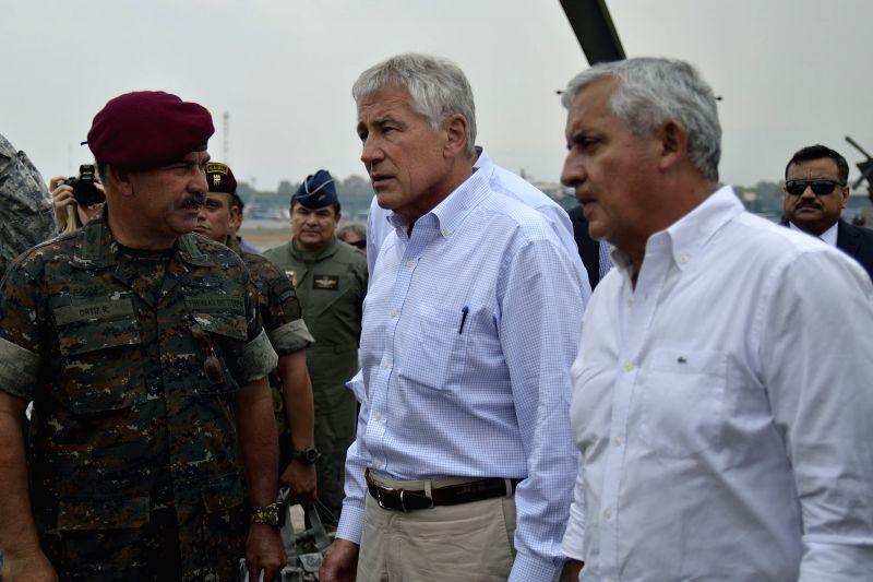 Guatemala's President, Otto Perez Molina (R), greets United States Defense Secretary, Chuck Hagel (C), at the Guatemalan Air Base, in Guatemala City, ...