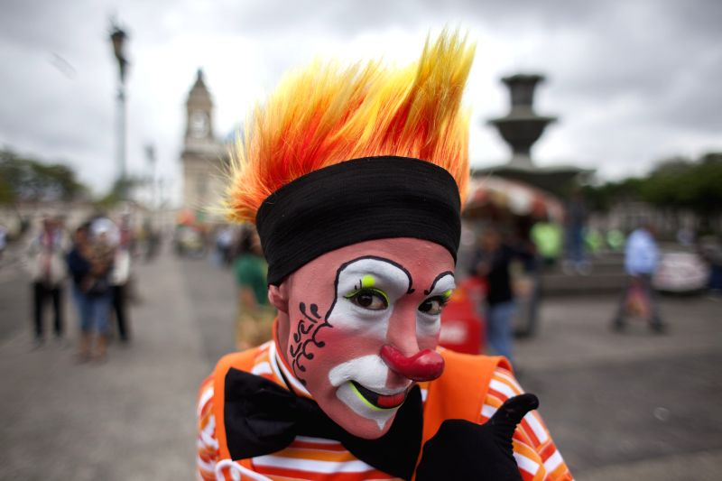 A clown poses for photos during the sixth Latin American Congress of Clowns parade, at the Historical Center of Guatemala City, capital of Guatemala, on July