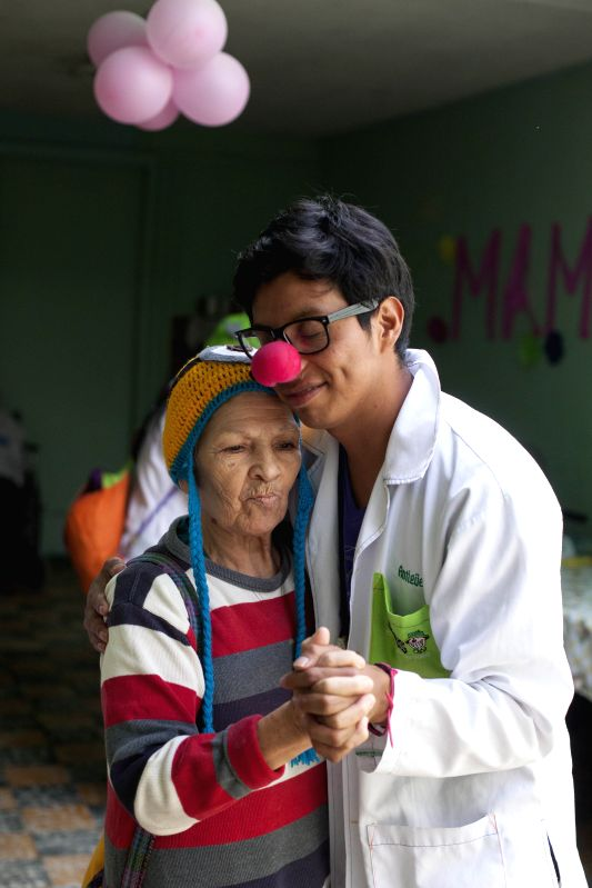 A volunteer of the organization Smile Factory dances with a woman in a asylum in Guatemala City, Capital of Guatemala on May 14, 2014. The organization Smile .