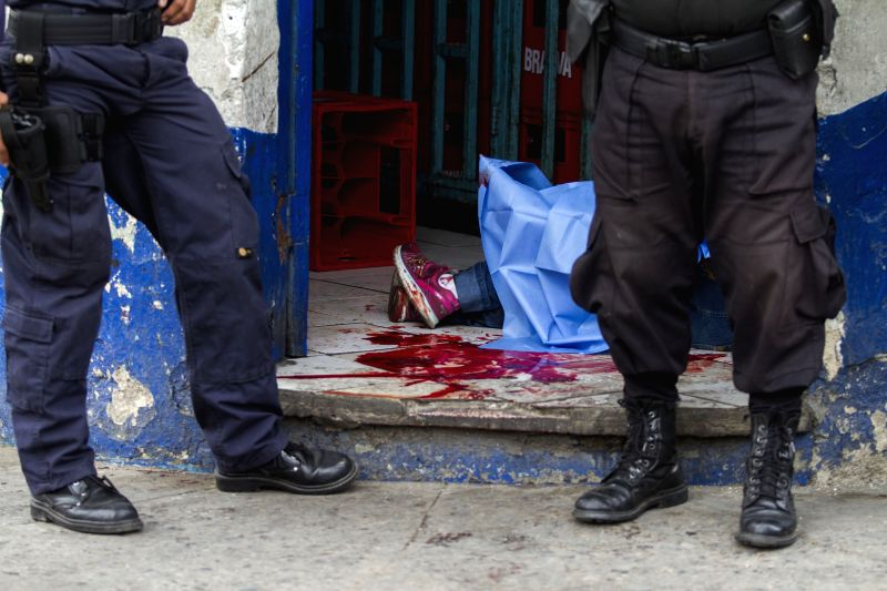 Policemen stand at a site where two women were murdered in a grocery store in Guatemala City, capital of Guatemala, on May 8, 2014. According to statistics of .