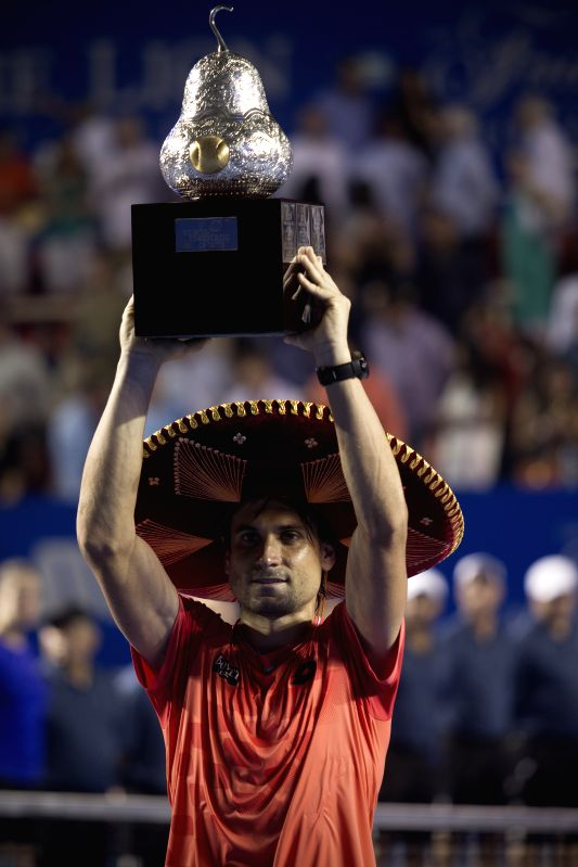 Spain's David Ferrer lifts the trophy after winning the men's singles final against Japan's Kei Nishikori on the Mexican Tennis Open 2015 tournament in Acapulco, ...