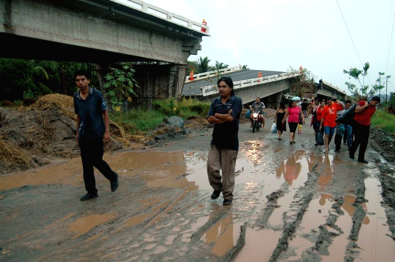 People walk next to a destroyed bridge on the federal highway Mexico-Acapulco near Tecpan, Guerrero, Mexico, on May 8, 2014. The strong earthquake jolted southwest ..