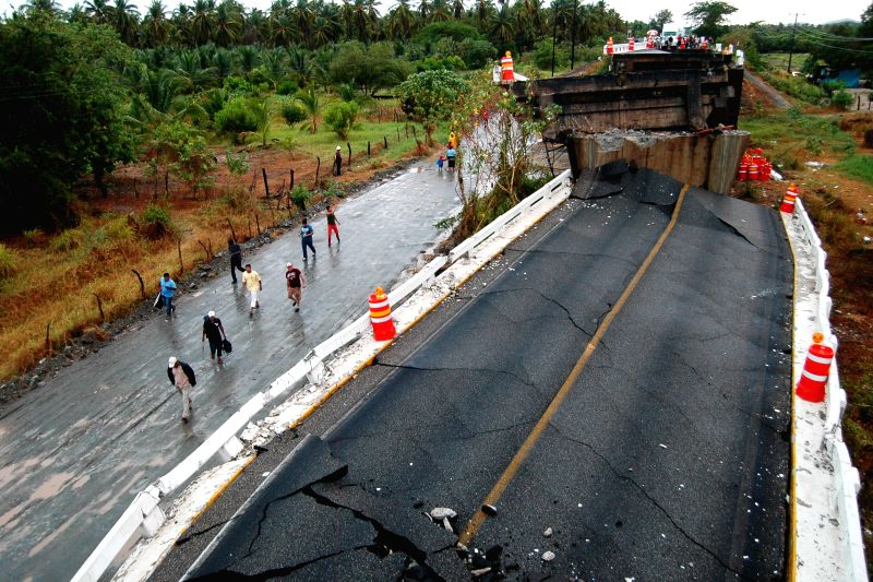 People watch a destroyed bridge on the federal highway Mexico-Acapulco near Tecpan, Guerrero, Mexico, on May 8, 2014. The strong earthquake jolted southwest Mexico ..