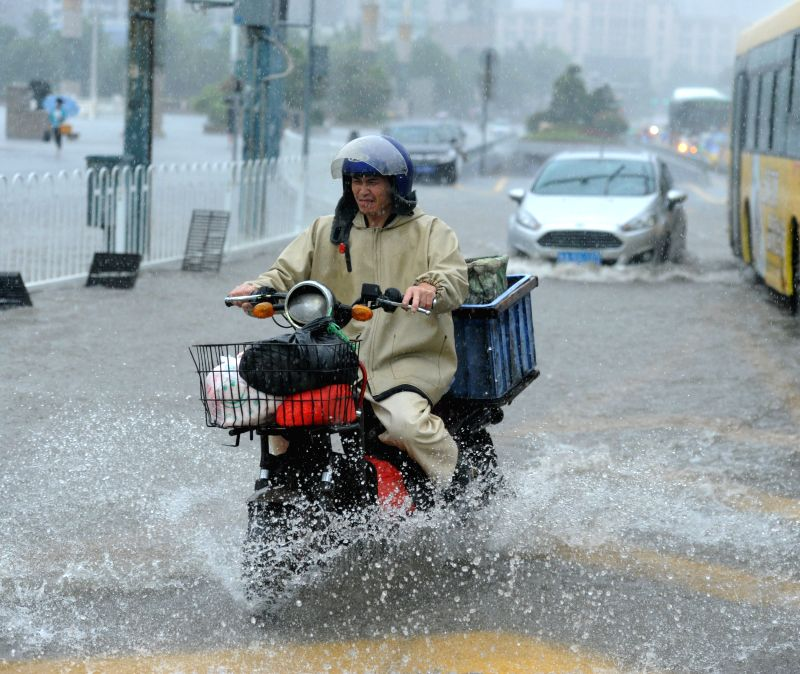 A man rides on a water-logged road in Guiyang, capital of southwest China's Guizhou Province, July 16, 2014.  Guizhou meteorological authority on Wednesday issued a
