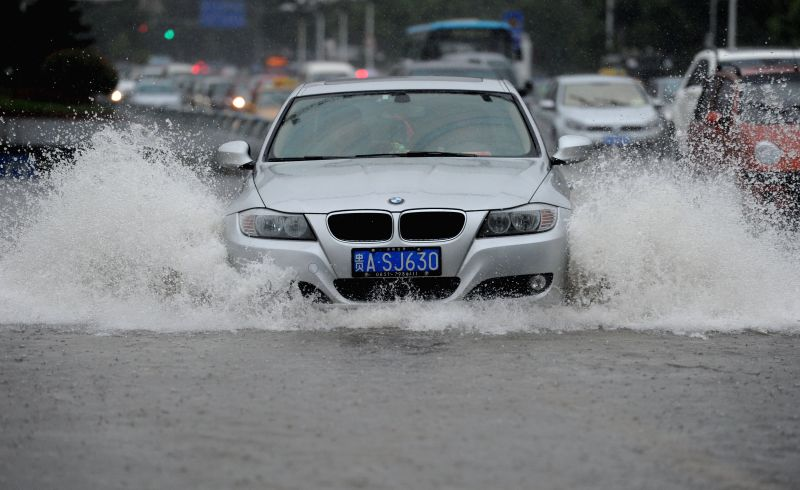 Cars move on a water-logged road in Guiyang, capital of southwest China's Guizhou Province, July 16, 2014.  Guizhou meteorological authority on Wednesday issued a ..
