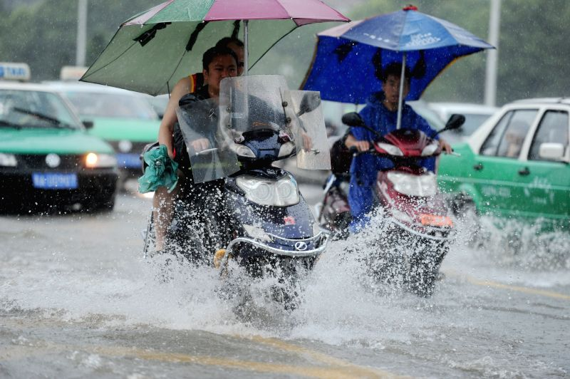 Citizens ride on a water-logged road in Guiyang, capital of southwest China's Guizhou Province, July 16, 2014.  Guizhou meteorological authority on Wednesday issued
