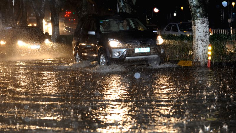 A car runs in the floods in Guiyang, southwest China's Guizhou Province, May 10, 2014. A heavy rain and hailstorm hit some regions of the province from late Friday. .