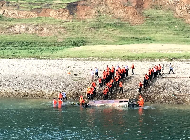 GUIYANG, May 24, 2019 (Xinhua) -- This photo taken by a cellphone on May 24, 2019 shows rescuers lifting up a capsized boat from a river in Zhenfeng County, Bouyei-Miao Autonomous Prefecture of Qianxinan in southwest China's Guizhou Province. Six peo