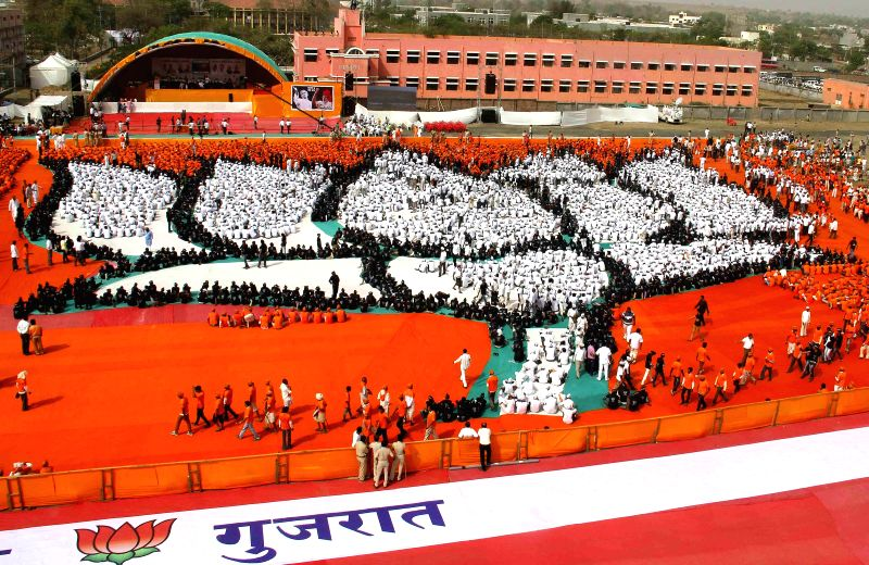 People sit in the formation of a lotus - the election symbol of BJP on party's foundation day at Dahod in Gujarat on April 6, 2015.