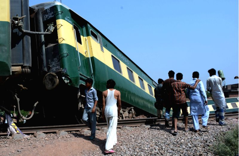 GUJRANWALA, April 18, 2017 - Locals walk past derailed compartments of a passenger train at the accident site in east Pakistan's Gujranwala, on April 18, 2017. At least 13 people were injured when ...