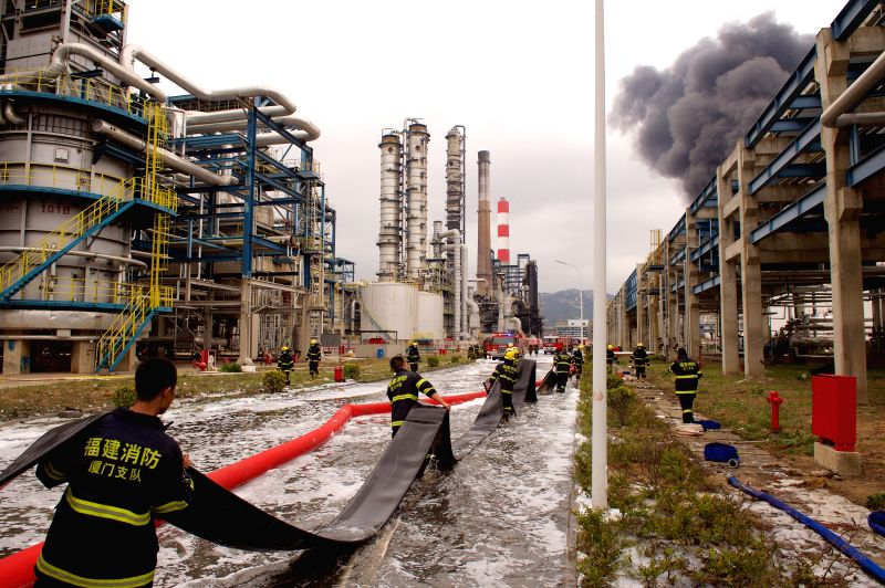 Firefighters work at the site of a burning chemical plant in Zhangzhou, southeast China's Fujian Province, April 8, 2015. A fire at the chemical plant that exploded ...