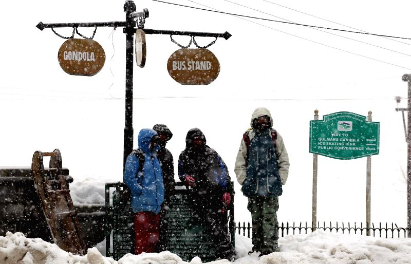 Tourists enjoy snowfalls in Gulmarg of Jammu and Kashmir on Feb 24, 2015.