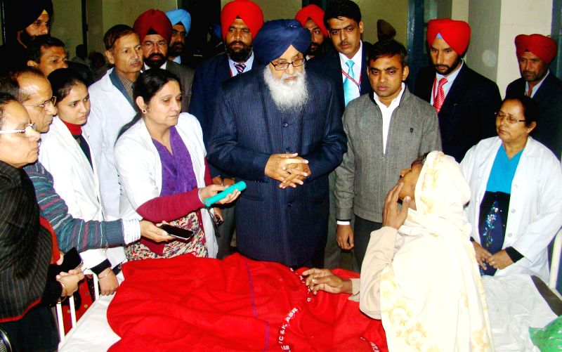Gurdaspur : Punjab Chief Minister Parkash Singh Badal meeting with the patients who lost their eyesight during an eye camp held at Ghuman in Gurdaspur village on Dec. 12, 2014. - Parkash Singh Badal
