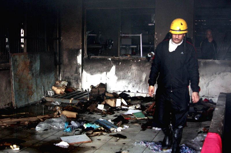 A fire fighter enters a Gurgaon factory premise after dousing a fire that broke out in the plant on Nov 30, 2014.
